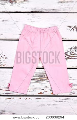 New cotton long pants for little girl. Toddler girl light pink cotton leggings with bows, old wooden background.