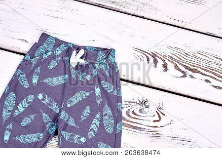 Toddler kids autumn patterned pants. Baby boy brand harem pants, white wooden background.