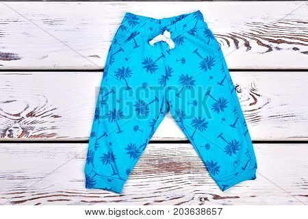 Baby boy blue printed trousers. Toddler boy palm tree print summer pants on wooden background, top view.