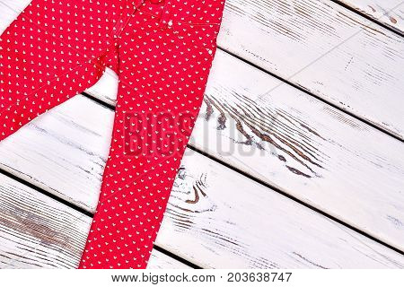 Girls new skinny colored trousers. Super skinny colored patterned jeans for girls, white wooden background.