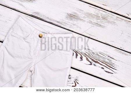 Childrens white denim trousers isolated. Girls high quality brand pants on old wooden background.
