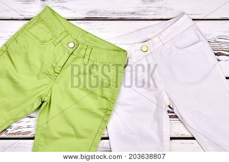 Green and white kids trousers. Childrens new colored trousers close up. Kids boutique clothes.