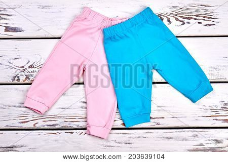 Collection of new kids trousers. Infant girls and boys colored pants on white wooden background. Childs organic apparel on sale.
