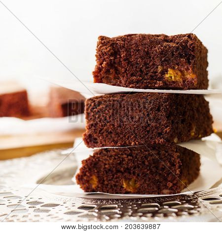 Stack three pieces of homemade chocolate brownies. Dark Chocolate cake with orange. Light background. Close up. Square image