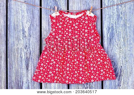 Baby red dress hanging on clothesline. Toddler girl patterned top drying on rope on vintage wooden background. Wet kids apparel in laundry.