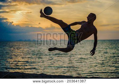 Kicking A Ball. Silhouette Of A Man On A Beach