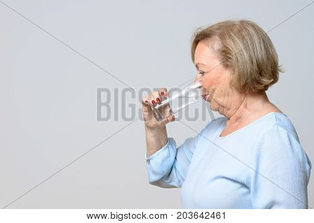 Senior Woman Drinking A Glass Of Fresh Water
