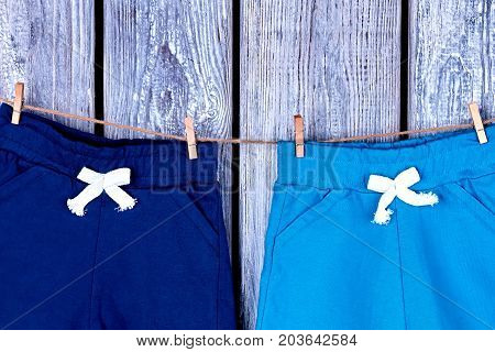 Kids pants hanging on rope. Childrens cotton shorts drying on clothesline on old wooden background.