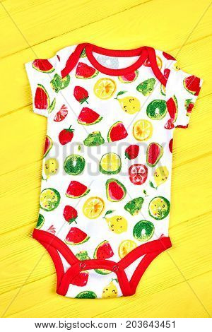Infants fruit print soft bodysuit. Baby cute cotton summer romper on yellow wooden background. Newborn kids high quality apparel.