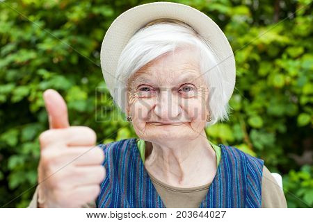 Elderly woman with mental disorder showing thumbs up in the park