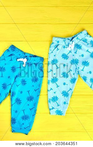 Toddler kids summer printed trousers. Childs blue pants on yellow wooden background. Kids brand outfit.