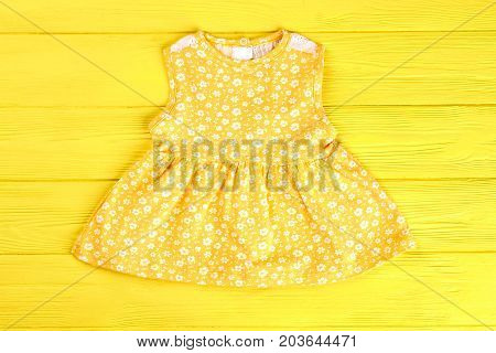 Baby-girl cute yellow sundress. Infant girl casual printed dress on yellow wooden background. Shop infants new apparel online.