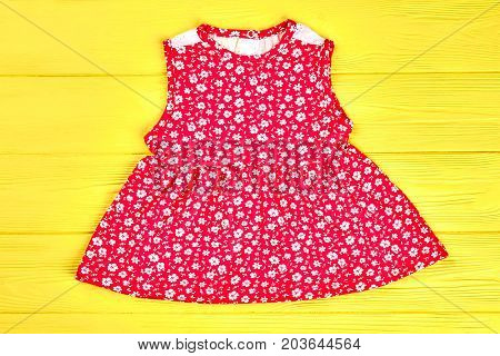 Little girls red patterned top. Baby-girl red natural printed dress on yellow wooden background. Kids summer apparel on sale.