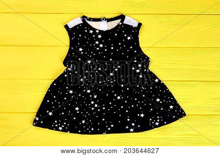 Baby-girl black stars print dress. Infant girl sleeveless cotton dress on yellow wooden background. Kids casual outfit on sale.