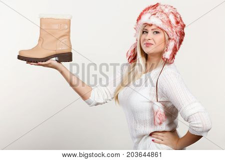Woman In Furry Winter Hat Holding Beige Boots