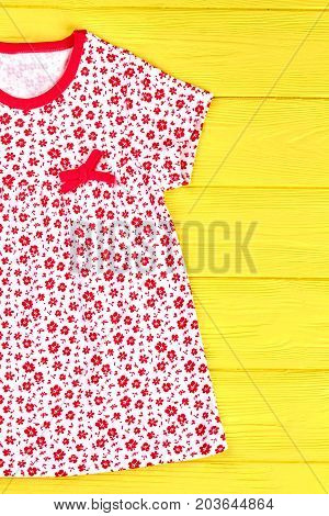 Infant girl new printed sundress. Little girl casual patterned dress on yellow wooden background. Kids natural apparel.