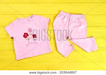 Baby-girl beautiful cotton suit. Infant girl pink t-shirt and leggings on yellow wooden background. Babies brand apparel on sale.