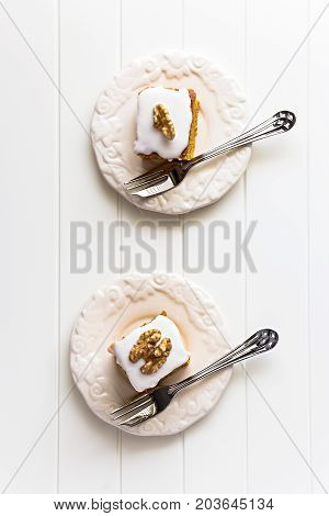 Two Pieces Nuts Carrot Cake With Icing Cream On Ivory Color Plate. Selective Focus. Close Up. Top Vi