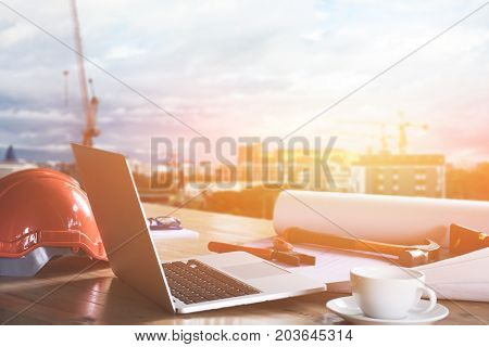 desk of Architectural project in construction site or office with mining light with building construction background