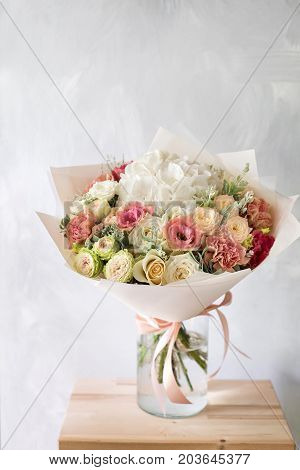 Close-up floral composition with roses and mix flowers on a light background. caramel-cream gamma