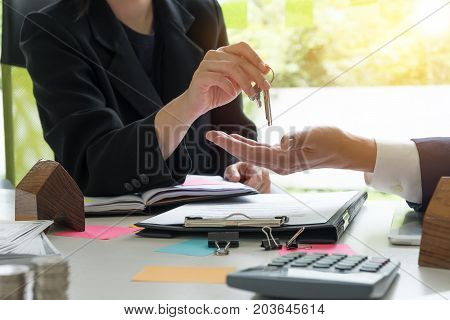 estate agent giving house keys to man and sign agreement with house model calculator agreement in office