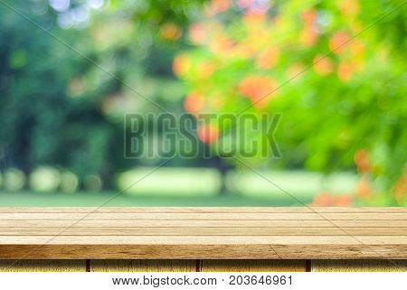 Empty wooden table over blurred tree with bokeh background for product display montage