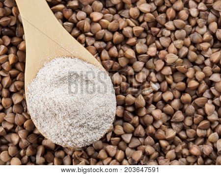 Buckwheat flour in wooden spoon and buckwheat grains. Whole-grain buckwheat flour on buckwheat grains background. Copy space. Top view or flat lay.