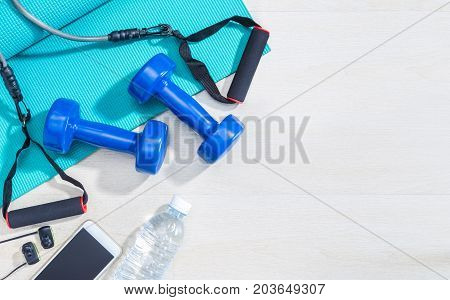 dumbbells excercise equipment gym yoga mat cellphone earphones and bottle of water on clean wood floor with strong bright morning light and hard shadow healthy and well being concept with room for text or copy space