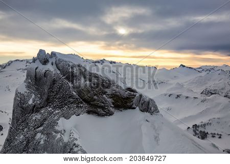Beautiful aerial landscape view of snow covered mountains with a colorful morning sky. Picture taken of Black Tusk in Garibaldi British Columbia Canada.