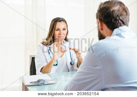 Female doctor removes the lid of a pressurized cartridge inhaler to a male patient at her office