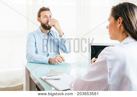 Male patient is inhaling a medicament from an aerosol inhaler in front o a female doctor at her office