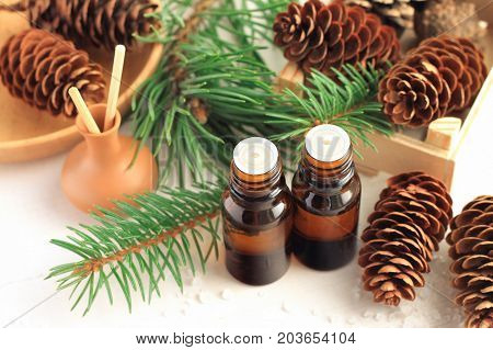 Glass dropper bottles of aromatic massage oil pine scent added to diffuser, spruce cones and green needles branches.