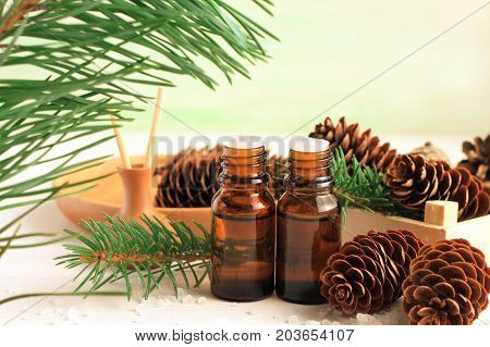 Pine essential oil in bottles, green fir tree branch with long needles, spruce cones. Winter herbal spa wood scented.