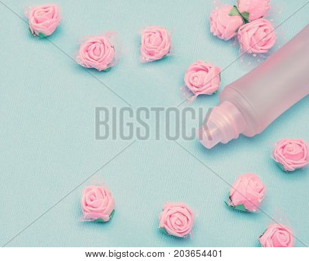 Perfume spray bottle and small pink roses on blue textured background. Vintage toning, copy space