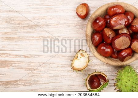 chestnut in bowl on white wooden background with copy space for your text. Top view.