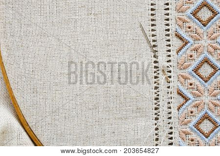 Embroidered fragment on flax by brown and beige cotton threads. Embroidery texture flat stitch. Ukrainian ethnic ornament. Hemstitch.