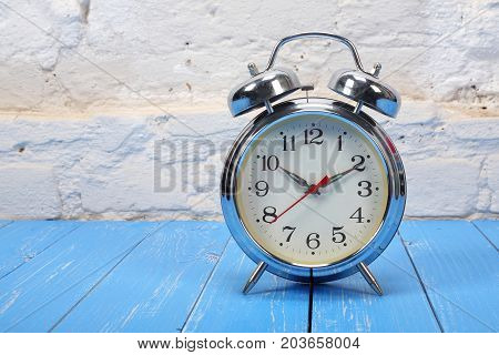 Vintage Alarm Clock - Old retro alarm clock on a blue wooden plank and brick wall background.
