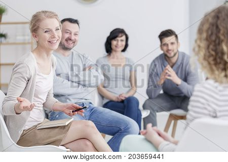 Smiling female therapist talking to people in support group sitting with a notebook