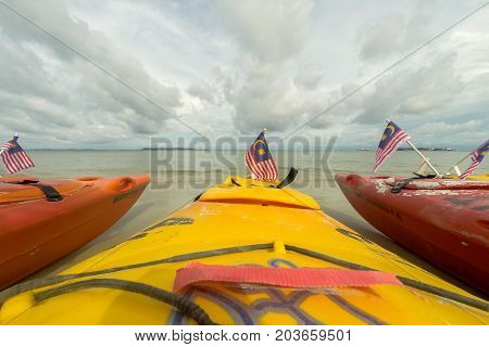Labuan,Malaysia-Sept 9,2017:Colorful sea kayaks on sand beach with Malaysia flag in Labuan island,Malaysia.Malaysia is the ideal place for water sports,like white water rafting,kayaking,scuba diving & sailing.