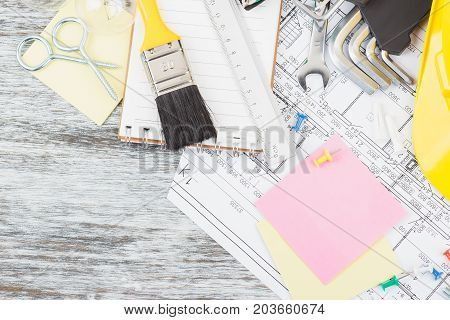Drawings, Notebook, Yellow Helmet, Paintbrush And Wrenches, Wooden Background
