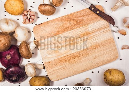Ingredients with fresh mushrooms on wooden background. Raw organic vegetables for healthily cooking on vintage table. Top view with copy space. Vegan or diet food concept.