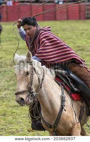 June 10 2017 Toacazo Ecuador: andean cowboy wearing traditional poncho on horseback handling a lasso