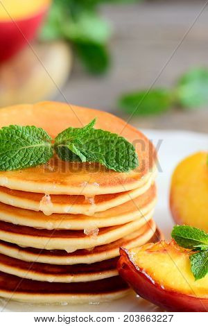Thin round fritters pile and fried slices of nectarines on a serving white plate. Simple and delicious fritters recipe. Closeup