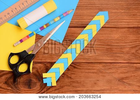 Paper bookmark for books or notebooks. Simple paper crafts for preschoolers and schoolchildren. Ruler, pencil, scissors, glue stick, colored paper sheets on a desktop. How to make a bookmark. Top view