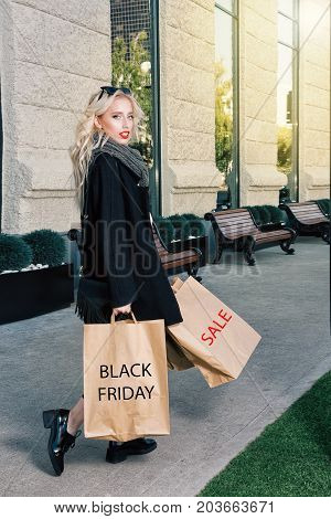 Young blonde woman with shopping bags. Fashionable shopper with Black Friday paperbag going out the mall. Black coat and shoes sunglasses