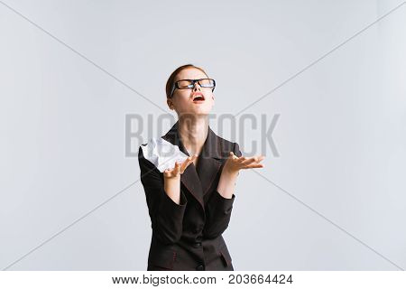 An angry business woman holds a lump of paper in her hand. I am tired of working. Has closed eyes