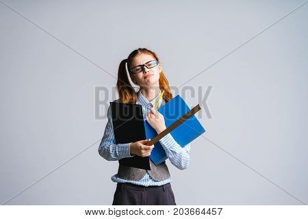 Tired woman teacher, holding a ruler and a folder with documents. Isolated on a gray background
