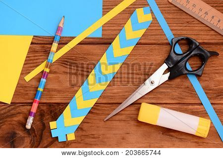 Yellow and blue paper bookmark. Scissors, glue stick, colored paper sheets, ruler, pencil on a wooden table. Light paper art projects. Paper craft for kids with folding paper. Top view