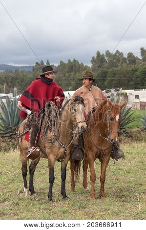 June 10 2017 Toacazo Ecuador: andean cowboys on horseback in traditional ponchos at a rural rodeo