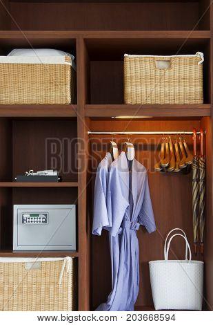 Muti function wooden wardrobe. Purple bathrobes hanging in wooden wardrobe.
